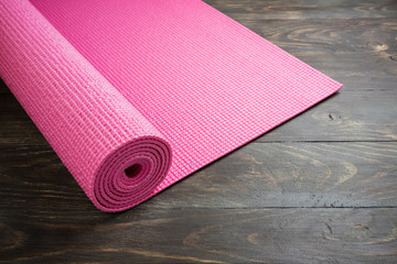 Pink yoga mat on wooden background. Equipment for yoga. Concept healthy lifestyle, sport and diet. Copy space