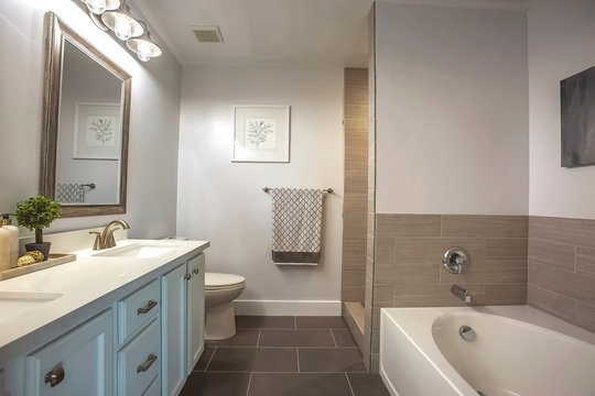 Bathroom interior with a bathtub in front of thee vanity area and mirror