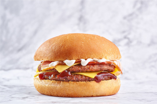 double cutlet burger with double cheese and bacon isolated at white marble background.