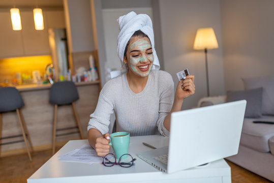 Woman with cosmetic face mask shopping online from her home. Leisure time at home. pPortrait of beautiful woman with facial taking a coffee at home while use internet with modern laptop computer