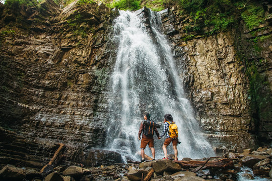 Man and woman hikers trekking a rocky path against the background of a waterfall and rocks. Hiker couple exploring nature.