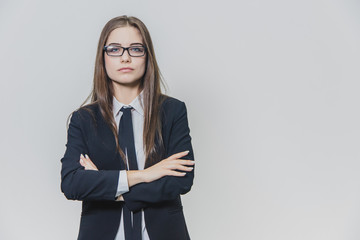 Charming confident businesswoman with black glasses is standing on the white background. Attractive female, professional model is isolated. She is smiling a little bit, crossing her well-groomed hands