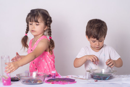 Kids making slime or handgum at home. Children mix ingredients for homemade diy toy slime.