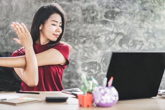 Asian female business woman stretching arm to relax muscle of shoulder blades sitting at office desk