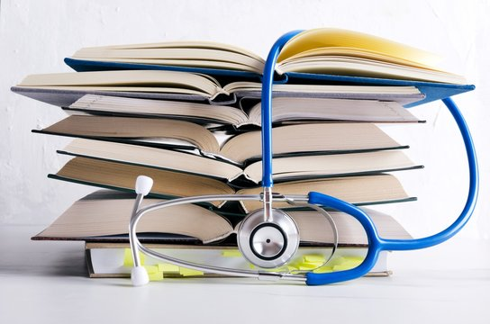 Medical knowledge. Pile of open books for medical student