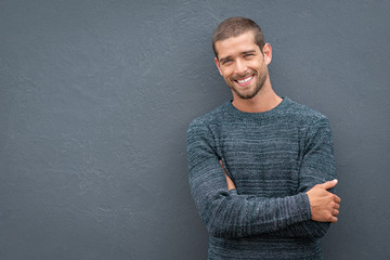 Smiling young man leaning against grey wall Wall mural