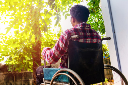 Man and wheelchair.he is sitting on wheelchair and see a tree.Despair,disabled person, lonely. Photo concept depression and Patient.