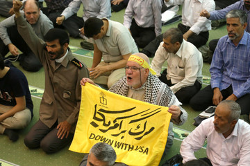 """A man holds a banner that reads """" Down with USA"""" during the Friday prayers in Tehran"""
