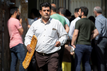 A man buys bread from a bakery in downton Tehran
