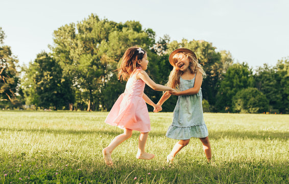 Horizontal image of two little girl dancing on the green grass in the park. Children enjoying summer days in the park. Two sisters having fun on sunlight outdoors. Childhood and friendship concept