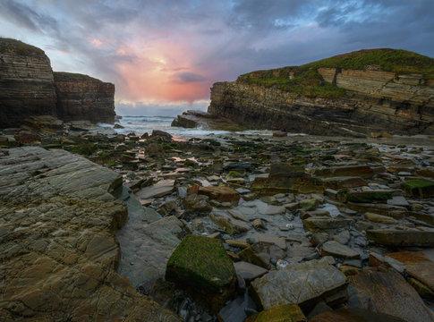Last rays of sunset on a rocky beach