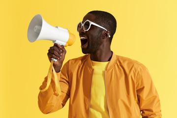 Advertising. Man screaming announcement in megaphone portrait