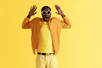 Scared man in sunglasses holding hands up on yellow background Wall mural