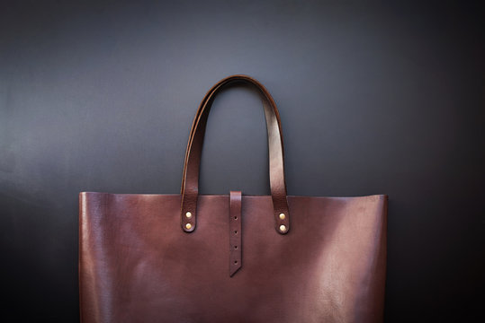 Elegant luxury leather brown bag dark background
