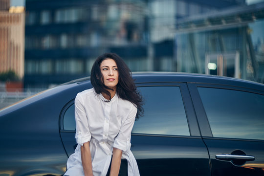 Smiling woman leaning on a car over modern office facade