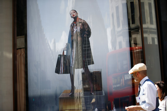 An advertisement containing a jacket with Burberry logo pattern is pictured at a window of a Burberry store in central London
