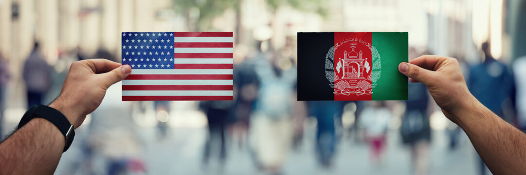 Two hands holding different flags, US vs Afghanistan on politics arena over crowded street background. Diplomacy future strategy, relations between countries