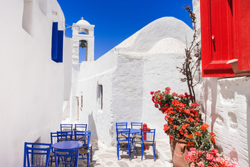 Traditional greek street with flowers and cafe tables in Amorgos island, Cyclades, Greece
