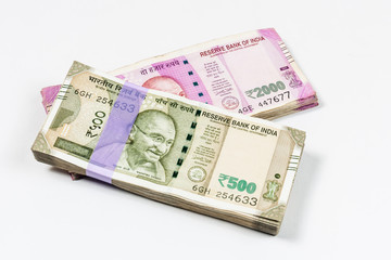 Bundles of Indian 500 and 2000 rupee notes in white background