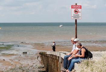People are seen sitting in front of an oyster bed close to a warning sign in Whitstable