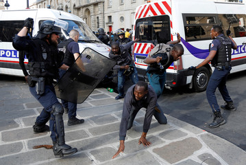 Riot police officers clash with undocumented migrants outside the Pantheon in Paris