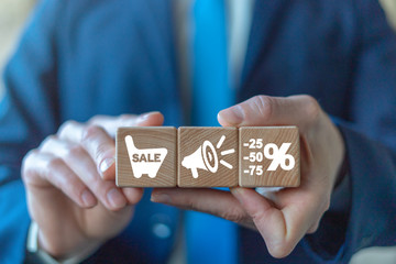 Businessman holding three wooden cubes with loudspeaker icon in middle cube. Promotion Mega Sale Discount concept.
