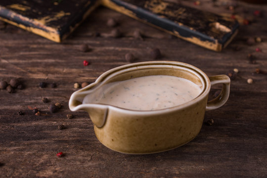 Creamy sauce with mushrooms and herbs in sauce-pan on rustic wood background