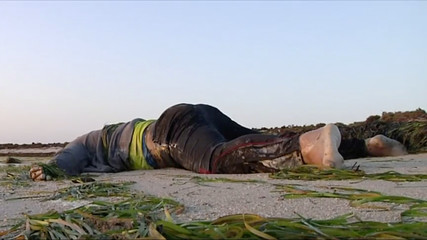 Body of a migrant washed up after a boat sank off the Tunisian coast lies on the beach in Zarzis
