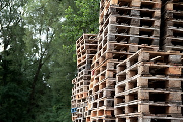 wooden pallets stacked high on top of each other in a companys factory yard in london no people stock photo