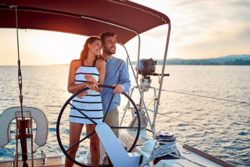 couple enjoying on luxury boat at sunset on vacation.