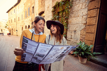 Two woman travel together. friends with map.