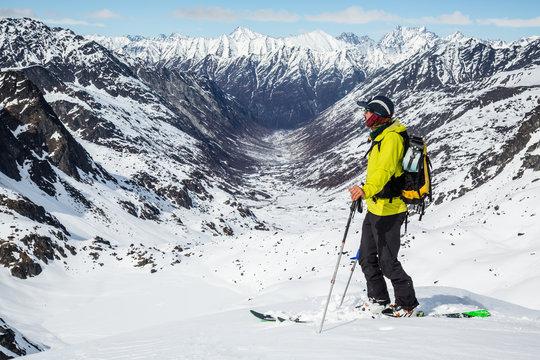 Skier standing above Snowbird Glacier looking down Bartholf Creek in Talkeetna Mountains