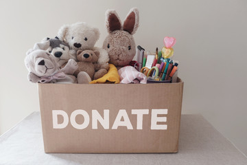 a box full of used toys, cloths, books and stationery for donation