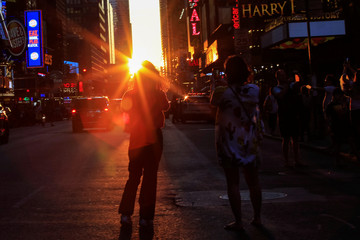 "People take pictures of the sun setting over Manhattan aligned exactly with the streets in a phenomenon known as ""Manhattanhenge"", in Times Square, in New York City"