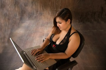 Asian plus size sexy , fat and overweight long hair model female in black dresses on brown studio background pose sitting use laptop.