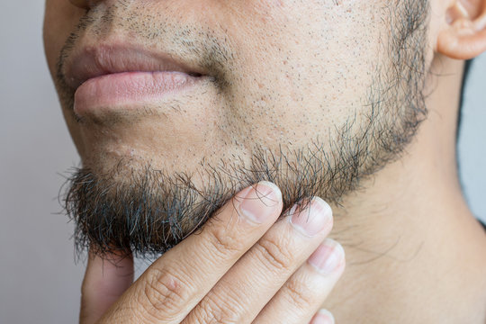 Cropped shot of Asian man touching his beard grows on a part of lower face. Beard is the collection of hair that grows on the chin, upper lip, cheeks and neck of humans.