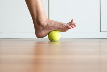 Woman massage with tennis ball to her foot in bedroom,Feet soles massage for plantar fasciitis,Close up