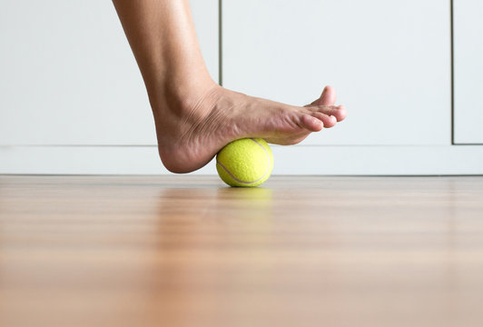 Woman massage with tennis ball to foot,Feet soles massage for plantar fasciitis