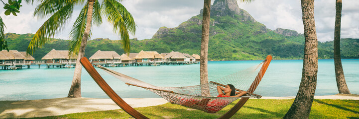 Wall Mural - Luxury vacation hotel panoramic Asian woman sleeping in hammock by overwater bungalow resort Bora Bora, Tahiti, French Polynesia. summer travel. relaxation getaway.