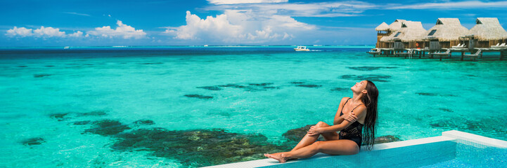 Wall Mural - Suntan beach vacation luxury woman sunbathing by overwater bungalow infinity hotel pool. Sexy Asian swimsuit model beauty banner panoramic on ocean blue beach background.