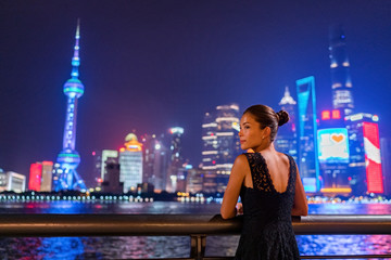 Photo Stands Shanghai Shanghai city night lights glowing in dark sky. Elegant lady by the Bund river in fancy lace dress evening gown. Asian model sightseeing.