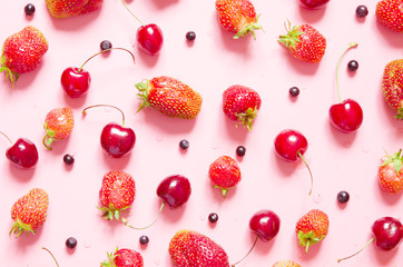 Strawberry, cherry and blueberry on pink background. Flat lay, top view. - Image