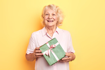 beautiful old lady holding a gift box and smiling. isolated yellow background. studio shot. Birthday, party concept.