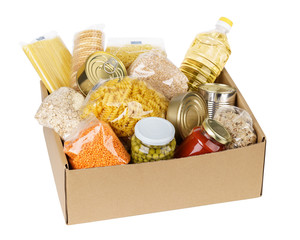 Open cardboard box with oil, canned food, cereals and pasta.