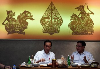 Head of Gerindra party Prabowo Subianto talks with Indonesia's president Joko Widodo during their meeting at FX Sudirman shopping mall in Jakarta