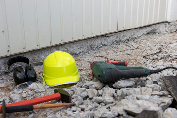 Electric hammer helmet and hearing protection lying on the rubble. Occupational safety at the construction site