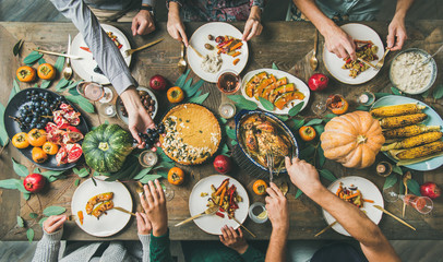 Thanksgiving, Friendsgiving holiday celebration. Flat-lay of friends feasting at Thanksgiving Day table with turkey, pumpkin pie, roasted vegetables, fruit, rose wine, top view Papier Peint
