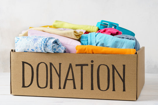 Donation box with various clothes on a table.