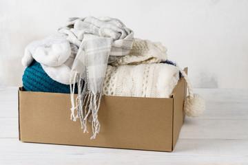 Winter clothes in a cardboard box. Seasonal clothing.