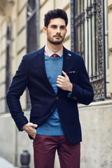 Attractive man wearing british elegant suit in the street. Modern hairstyle.